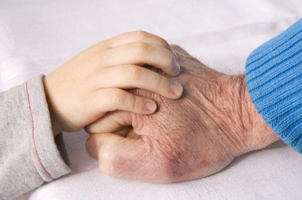 ребенок положил свою руку на руку старика
