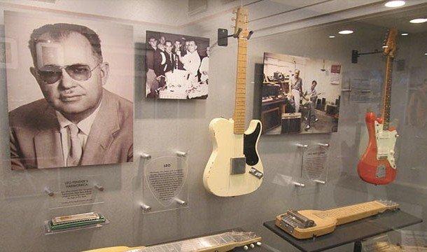 Портрет Лео Фендера на стене и гитары