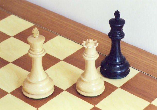 Чёрный король и белые король и ферзь на шахматной доске