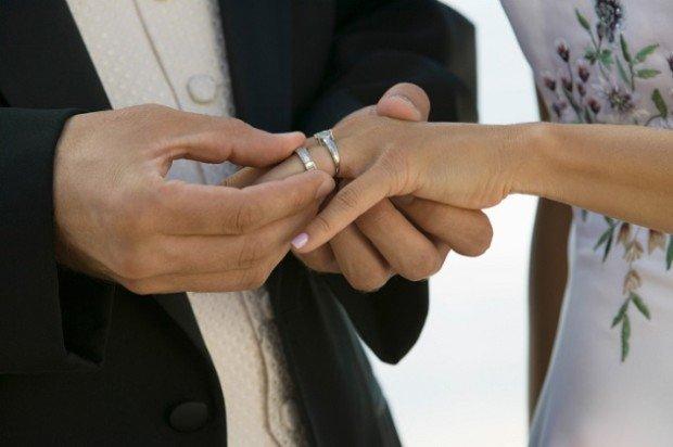Мужчина надевает женщинекольцо на палец рядом с помолвочным