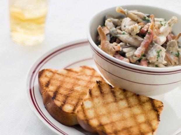 Блюдо из лягушачьего мяса и поджаренный хлеб на тарелке