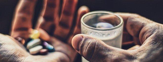 Лекарства и стакан воды в руках