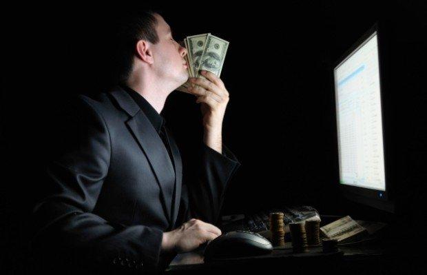 Мужчина со 100-долларовыми купюрами перед экраном