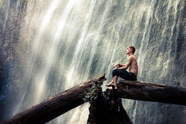 Парень сидит на дереве возле водопада