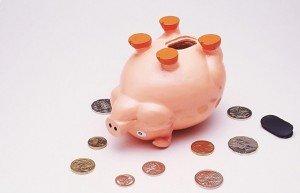 Раскрытая свинья-копилка и монеты вокруг