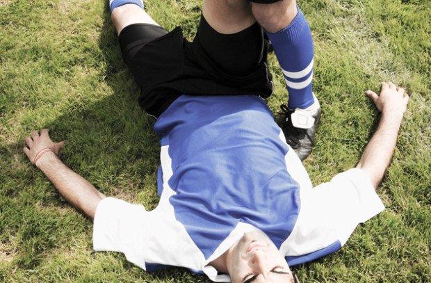 Футболист, лежащий на газоне