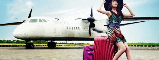 Улыбающаяся девушка с чемоданами на фоне самолёта