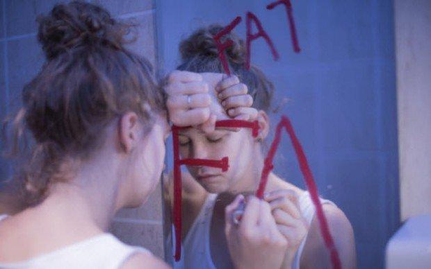 Девушка пишет на зеркале слово Fat
