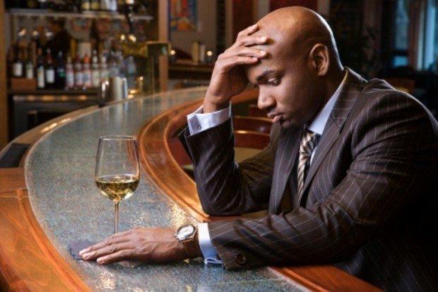 Мужчина с бокалом выпивки сидит за барной стойкой