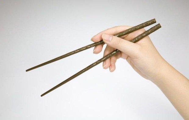 Палочки для еды в руке