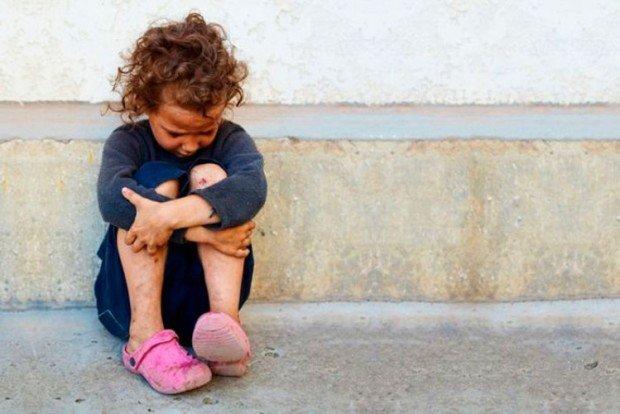 Плачущая девочка, сидящая на тротуаре