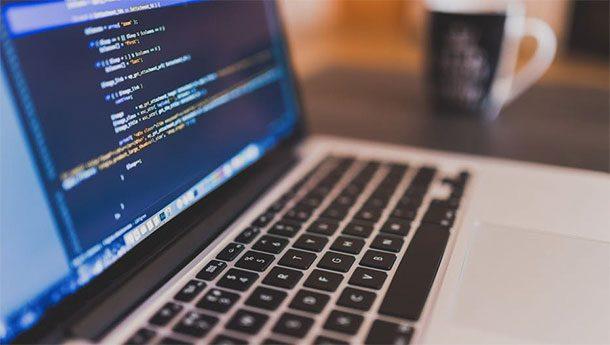 Открытый работающий ноутбук и чашка кофе