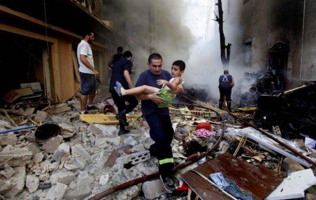 Мужчина несет ребенка по руинам дома