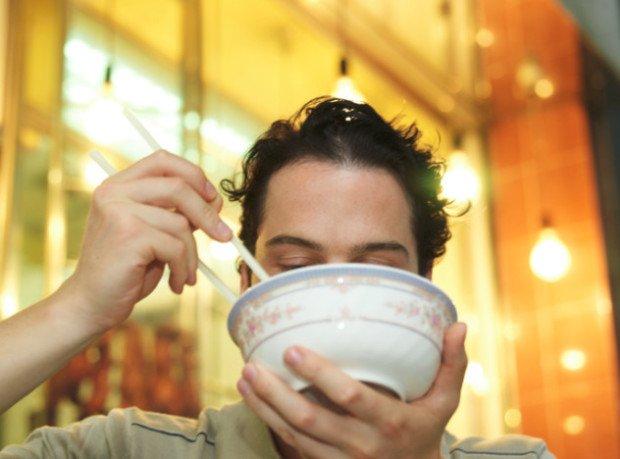 Мужчина ест палочками для еды из стеклянной миски