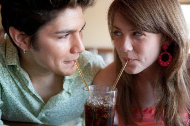 Девушка и парень пют колу из одного стакана через соломинки