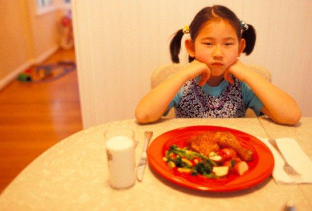 Девочка-кореянка за обеденным столом перед тарелкой с едой