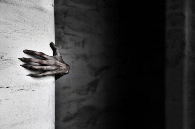 Чёрная рука чудовища, вылезающего из-за стены