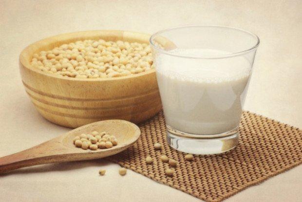 Соя в деревянной миске и ложке и соевое молоко