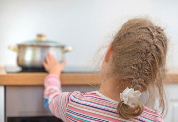 Девочка прикасается к горячей кастрюле