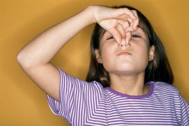 Девочка зажимает нос