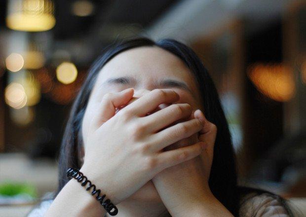 Девушка закрывает рот ладонями
