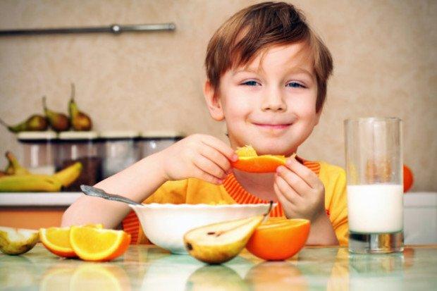 Мальчик кушает апельсин