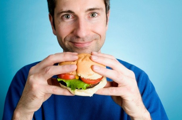 Мужчина держит гамбургер