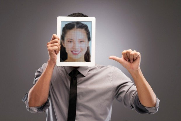 Парень, закрывший лицо фотографией девушки