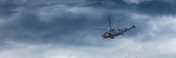 Вертолёт летит над морем во время шторма