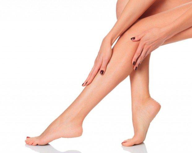Женщина поглаживает свою ногу