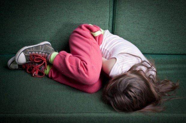 Девочка лежит на диване, свернувшись калачиком