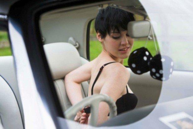 Девушка застёгивает бюстгальтер в автомобиле