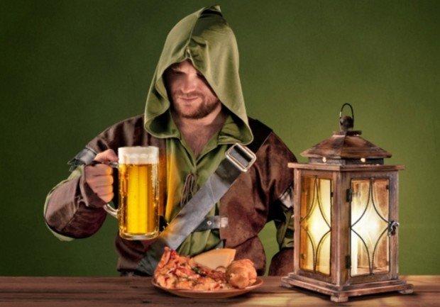 Мужчина в капюшоне с бокалом пива в руке