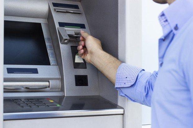 Мужчина вставляет карту в банкомат