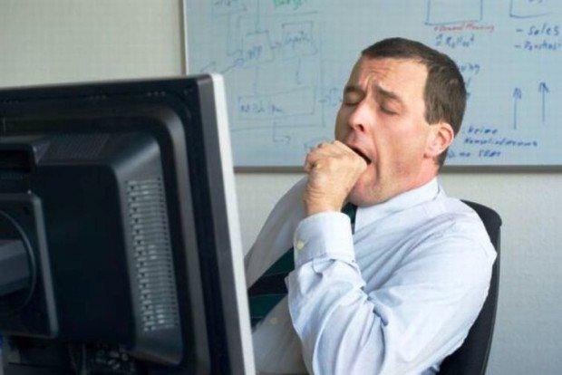 Мужчина зевает перед компьютерном