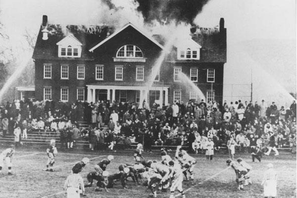 Дети играют в футбол перед горящей школой