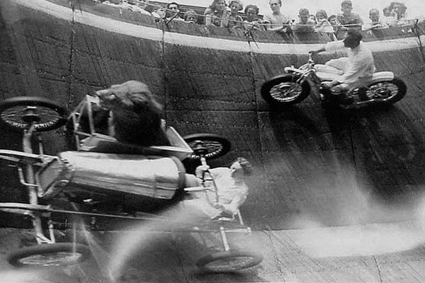 Лев в мотоцикле, едущем по отвесной стене