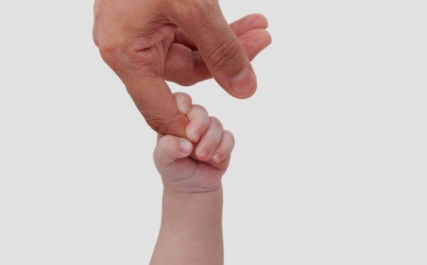 Новорожденный держится за палец взрослого