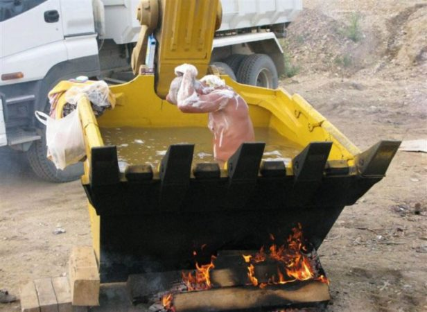 Мужчина моется в ковше экскаватора