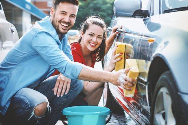 Парень и девушка моют машину