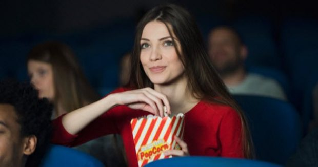 Девушка с попкорном в кинозале