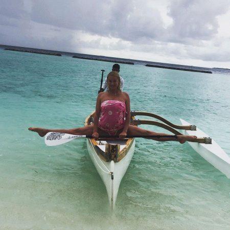 Знаменитая балерина сидит в шпагате на лодке
