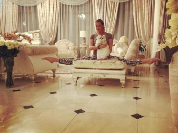 Анастасия Волочкова в шпагате сидит у себя дома на кушетке