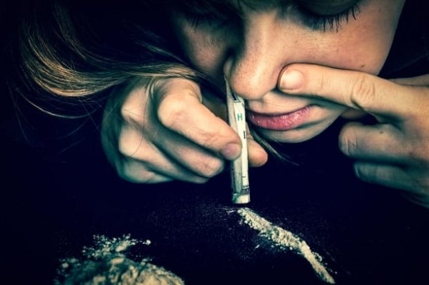 Девушка нюхает кокаин