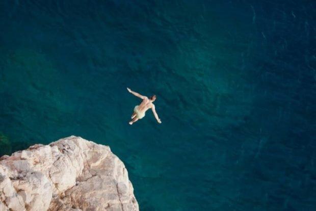 Человек прыгает в воду с обрыва