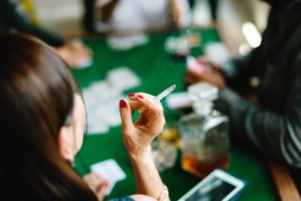 Женщина курит за игральным столом