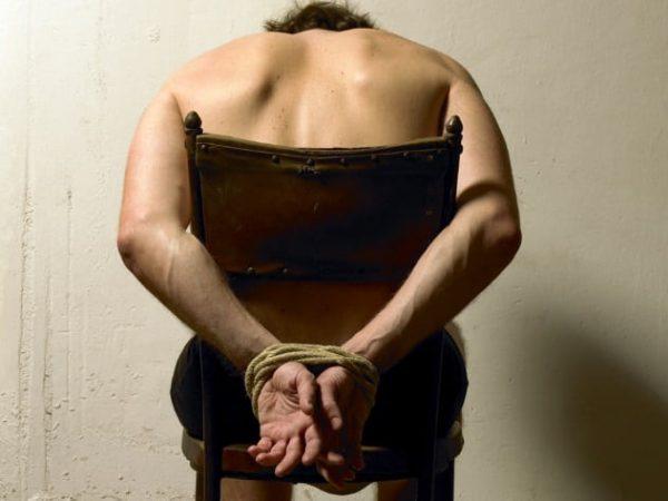Человек привязан к стулу
