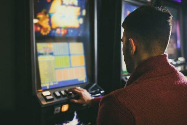 Мужчина сидит за игровым автоматом