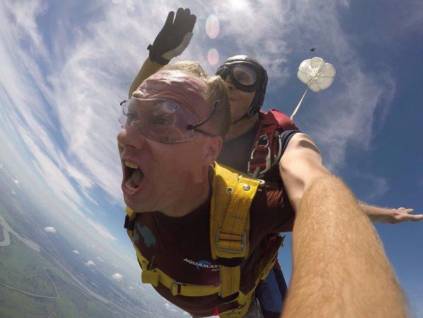 Мужчина в полёте с парашютом