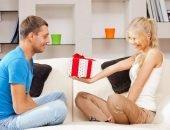 Девушка протягивает коробку с подарком парню